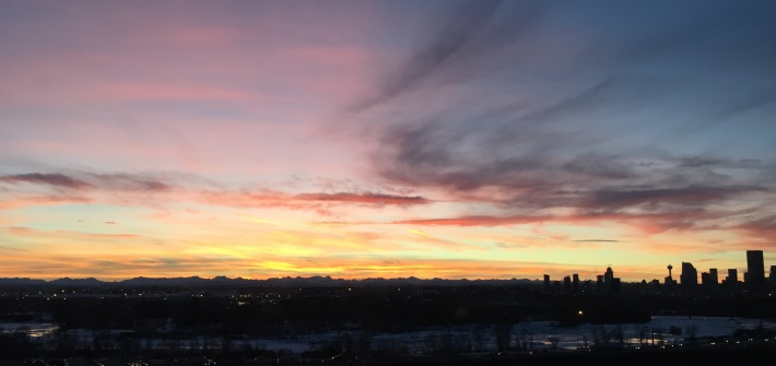 Calgary's skyline shadow over a sunset backdrop.